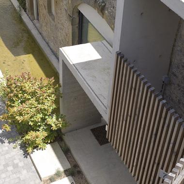 Vue de la zone d'entrée principale en béton architectonique et détail du claustra en bois du balcon - Lili's garden - architecture d'intérieur
