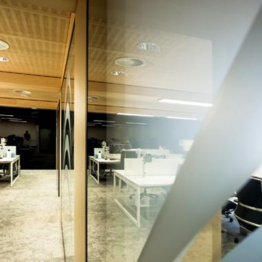 Vue sur cloison vitrée et bureaux open space